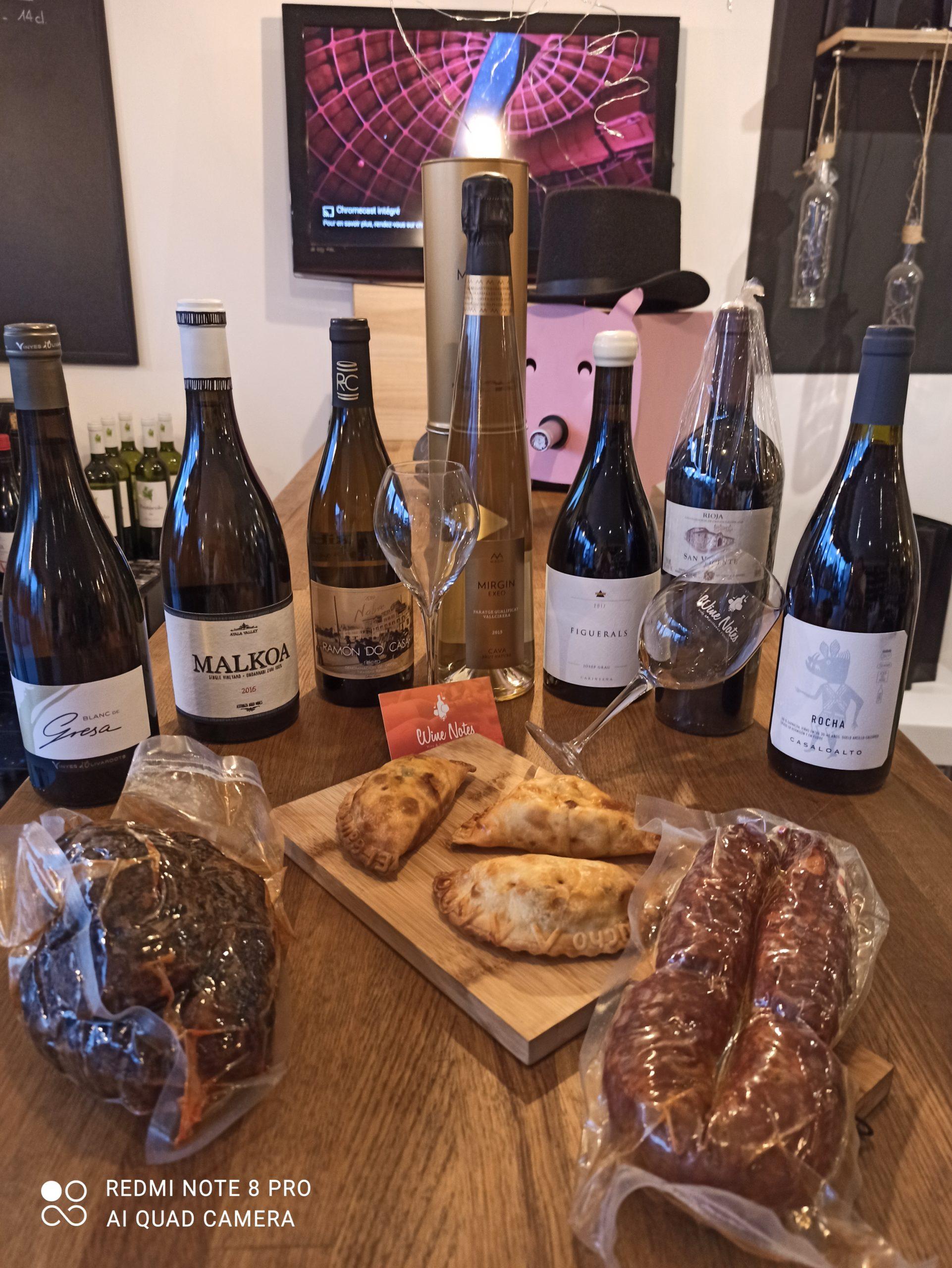 Planche de charcuteries, bouteilles de vins et empanadas disposés sur un table chez le caviste